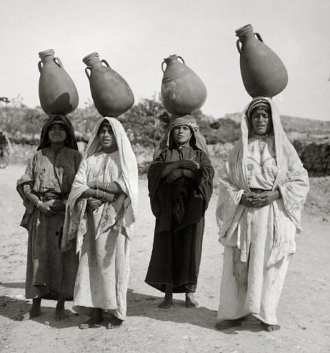 Palestinian women carrying large water jugs